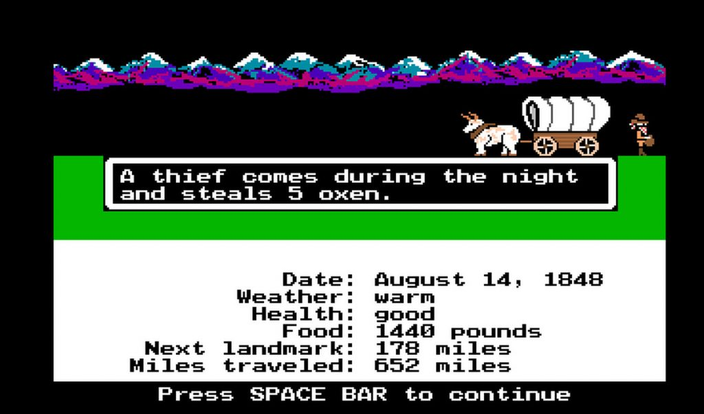 """Oregon Trail Gameplay screen. The image shows an 8-bit covered wagon and an ox, with a thief leaving the scene of the crime. The text reads, """"A thief comes during the night and steals 5 oxen. Press SPACE BAR to continue."""" The Oregon Trail, MECC, Brøderbund, 1971."""