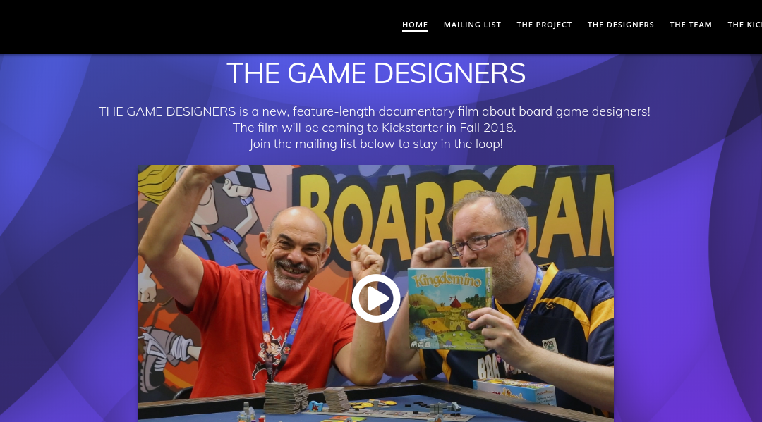 "A screenshot of the home page for The Game Designers, which reads, ""THE GAME DESIGNERS THE GAME DESIGNERS is a new, feature-length documentary film about board game designers! The film will be coming to Kickstarter in Fall 2018. Join the mailing list below to stay in the loop!"" And features a screenshot of two white men, one of whom appears to be cheering, while another holds up a copy of ""Kingdomino."""