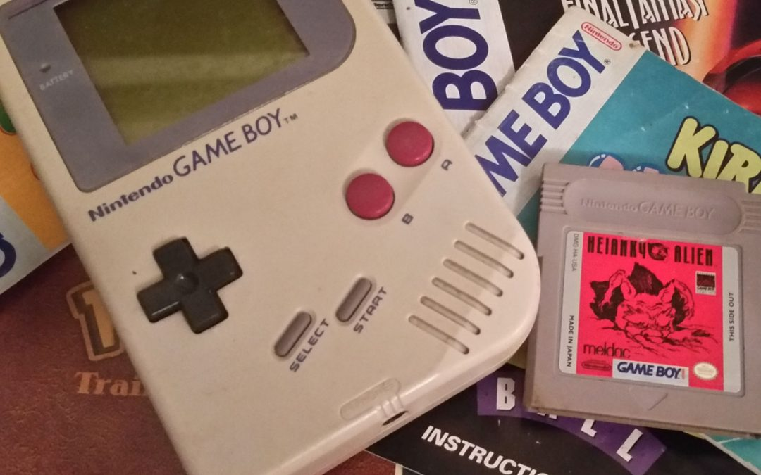 Photo of a Gameboy and cartridge on top of a pile of game manuals. Photo credit: tiakall.