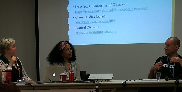 (L-R) Emily Marlow, Chella Ramanan, and Dr. Ewan Kirkland sitting next to each other on the Game Studies in the UK panel. A projector screen behind them lists useful game studies sources.
