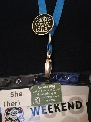 """Close-up of a Nine Worlds lanyard and badge. On the badge is a she/her pronoun sticker, and an Access Ally sticker. Attached to the lanyard is a """"anti-social club"""" pin."""