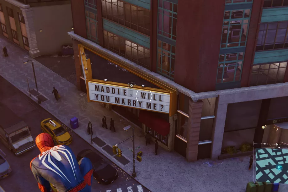 """A screenshot from Marvel's Spider-Man showing Spider-Man crouched on a building. Below him is a theater marquee reading, """"MADDIE, WILL YOU MARRY ME?"""" Marvel's Spider-Man, Insomniac Games, Sony Interactive Entertainment, 2018"""