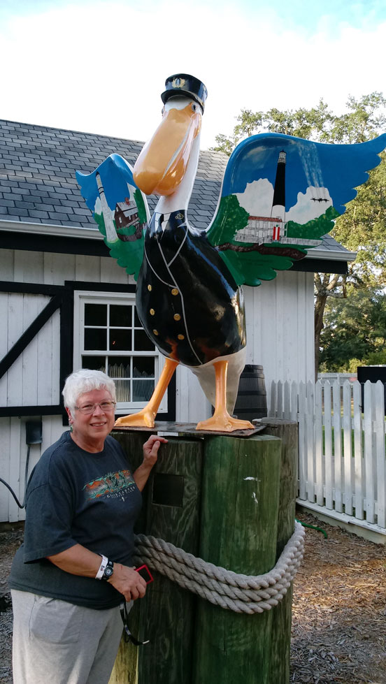 Photograph of Jean standing next to a large painted pelican.