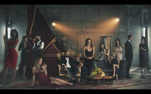 A group shot of formally dressed people are staged along a makeshift, theatrical looking setup in a warehouse. Two spotlights beam in the background. One man, centered, is seated on a throne-like chair. Super Seducer 2, RLR Training Inc, Red Dahlia Interactive, 2018