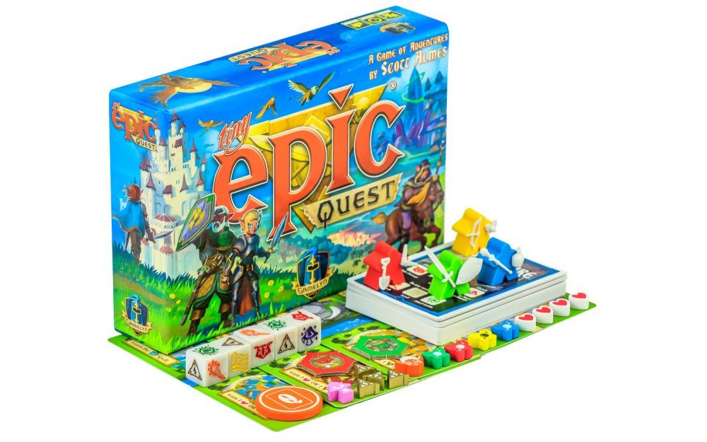 """A photo of """"Tiny Epic Quest."""" The game includes five six-sided dice with symbols instead of numbers, four """"meeples,"""" a deck of cards, and various tokens and layout pieces. All are incredibly colorful, leaning towards red, yellow, green, and blue."""