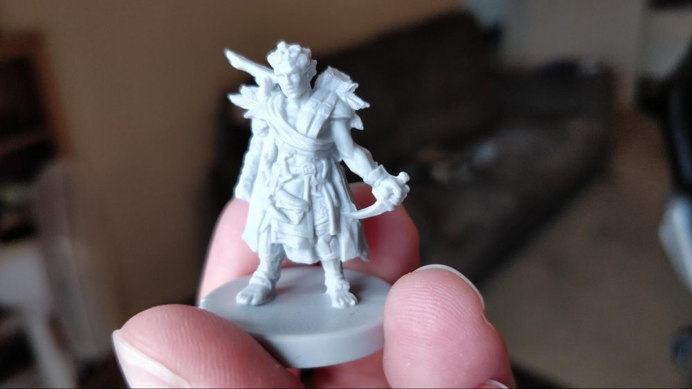 A photo of one of many player figures. This figure is wearing layered sleeveless robes and holding a curved dagger. He's laden with pockets and heavy cloth, and appears to have things strapped to his back as well.
