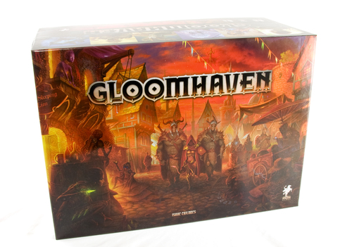 A photo of Gloomhaven's box. The box is rectangular, wider than it is tall, and clearly deep. The illustration on the cover is all oranges and browns, making the space look firey without any obvious fire. In the center of the illustration, two guards in bristling armor march towards the camera, led by a smaller figure wearing a hood and carrying a sword.