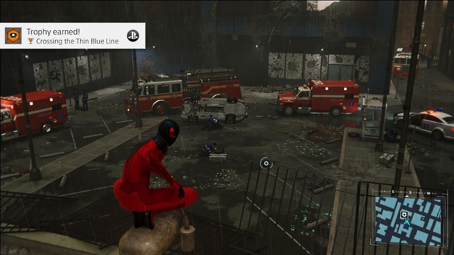 """Spidey crouches on an overhang, surveying the aftermath of a crime scene. Fire trucks and ambulances ring the buildings; across the road, a glass display window is shattered. The achievement text reads: """"Trophy earned! Crossing the Thin Blue Line."""" Marvel's Spider-Man, Insomniac Games, Sony Interactive Entertainment, 2018"""