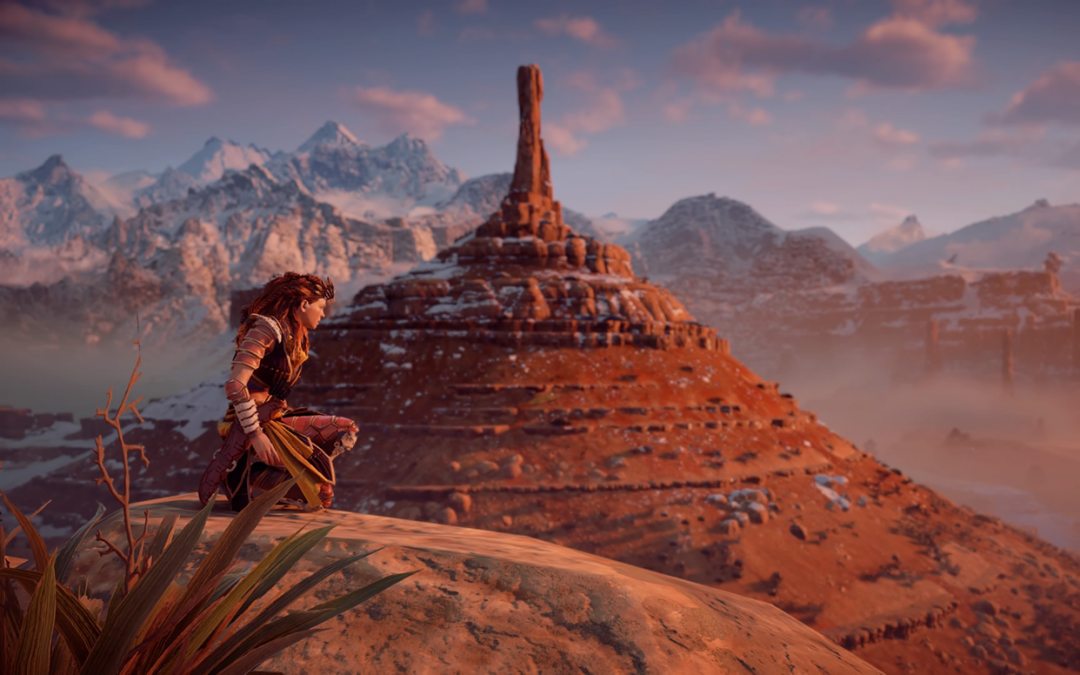 A screenshot of Aloy crouched on a bluff in front of distant hills and mountains.