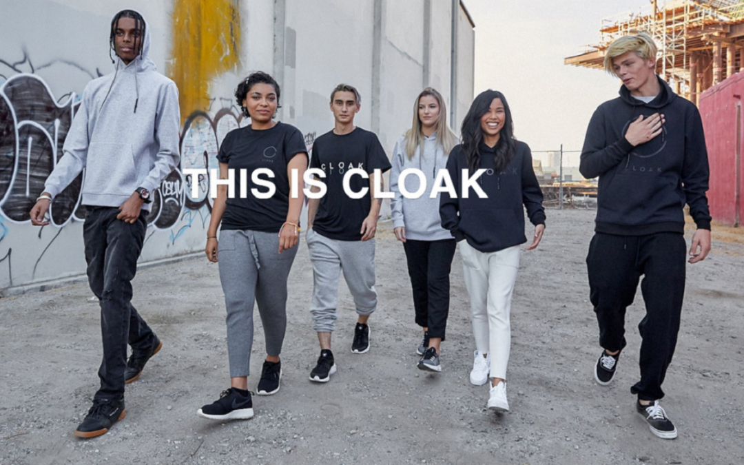 From cloakbrand.com. White letter that says THIS IS CLOAK in front of six people walking on the street. These people are wearing casual clothes and are a mix of people of color and white people.