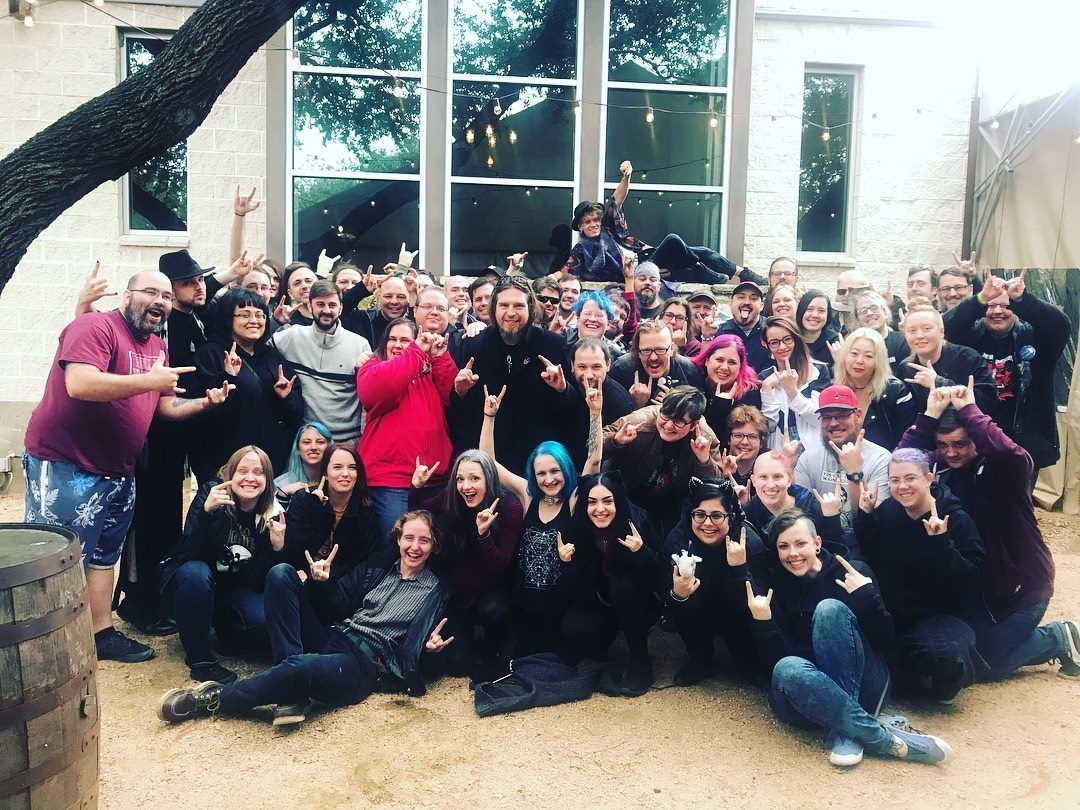 """A photo of a large group of LARP participants, with most of them holding their hands up in the """"rock on"""" devil horns symbol."""