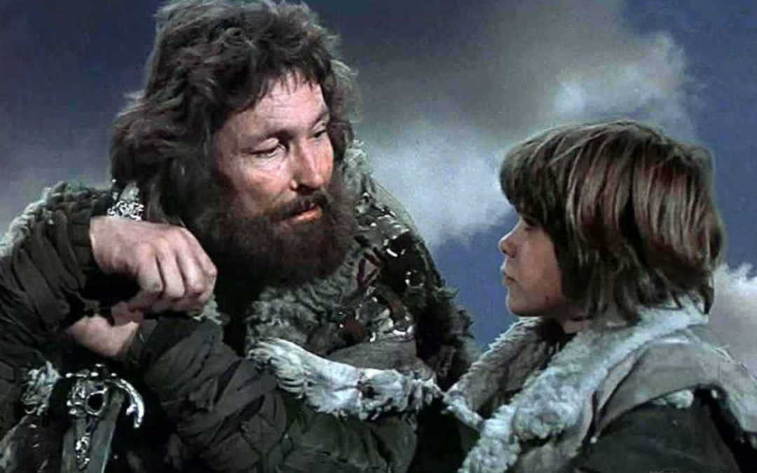 A picture from Conan the Barbarian (1982) of young Conan and his father. They're bundled in coats and his dad has a sword.