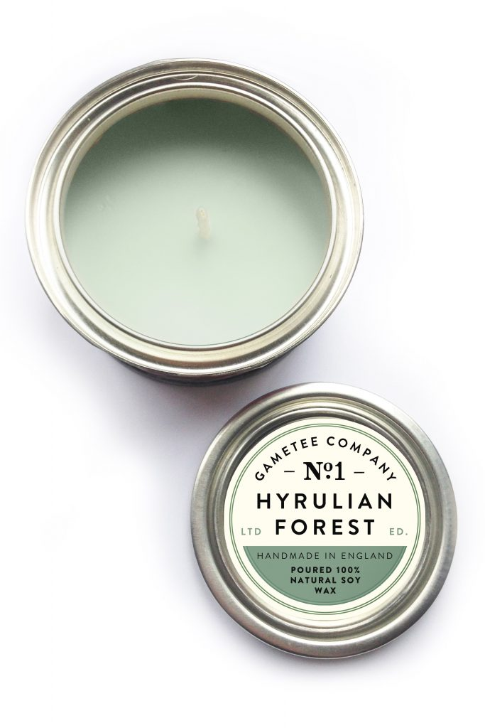"A photo of a green candle. A label on the lid reads ""GameTee Company No. 1. Hyrulian Forest. Handmade in England. Poured 100% Natural Soy Wax."""
