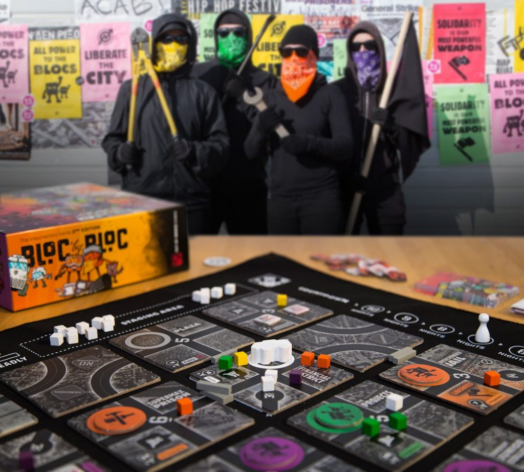 An image of Bloc by Bloc's game board, with four black-clad figures in the background wearing colorful bandanas and holding crowbars, wrenches, bolt cutters, and a black flag. Bloc by Bloc, Out of Order Games, 2018.