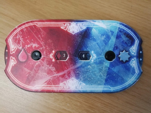 Cardboard oval, half red (health) and half blue (experience). Rotating dials allow the player to keep track of their health and experience during a scenario.