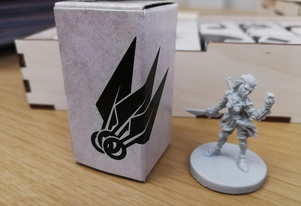 White rectangular box, with three throwing knives icon on it stands to the left of a Scoundrel plastic figure. The Scoundrel is female, snarling, and armed.