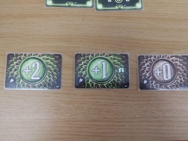 Three cards show attack modifier numbers: +2, +1, +0. The modifier numbers are large and in the center of the cards, surrounded by scaly design work.
