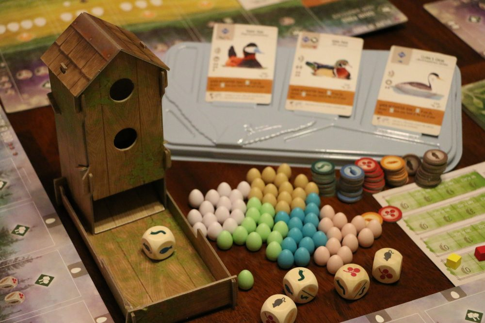 A photo of Wingspin's pieces, including a dice tower, cards, board, dice, and small multicolored eggs.