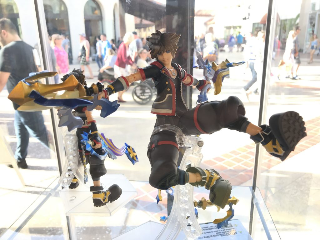 A figure of Sora with his keyblade blasters in an action pose in a Display Case at Disney Springs.