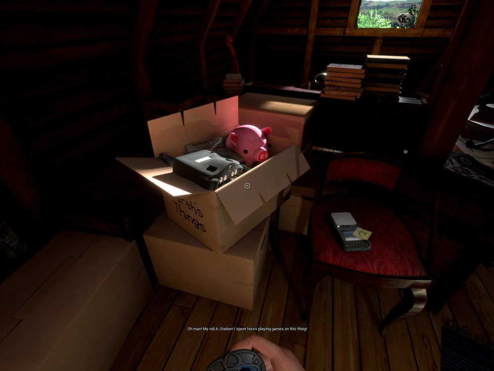 """A screenshot from What Never Was, showing a box labeled """"Sarah's Things"""" containing a pink stuffed pig and a game console. The box is in a dimly lit attic, surrounded by piles of books, knick knacks, and other boxes. A caption reads, """"Oh man! My old A-Station. I spent hours playing games on this thing."""""""