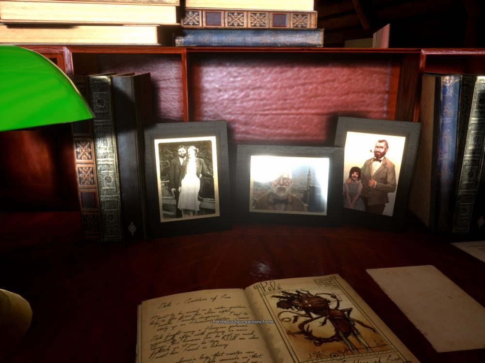 """A screenshot of What Never Was depicting a desk containing several photos and books. A green glass bankers lamp peeks into the left of the frame, and the desk is made of rich red wood. A notebook is open, and the three photos propped up against the back of the desk are framed and look old. Text at the bottom of the screen reads """"I...I know you have questions for me."""""""