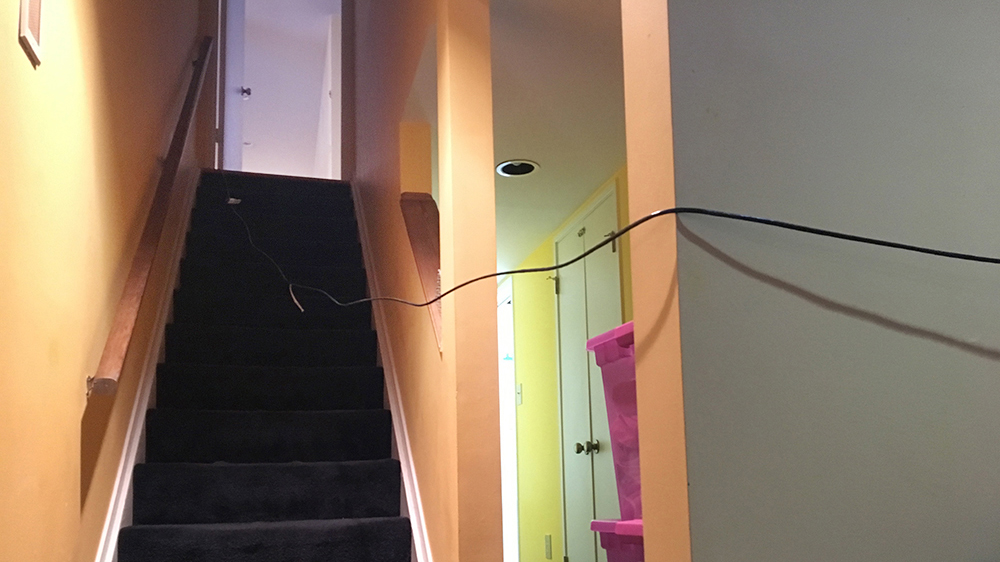 A photo of our day 1 ethernet setup. The cord snakes into a doorway, down a flight of stares, across another doorway, and into our basement den. It lifts off the stairs at the landing, and is neck-height by the time it blocks the doorway. It also crosses ACROSS the stairway, meaning we have to lift it up or duck under it to get to a) the bathroom, and b) upstairs. Photo by author.