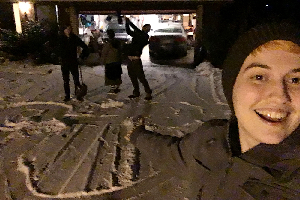 A real-life selfie of the author, mimicking Sora's grin-and-gesture selfie pose and indicating a giant Micky Mouse head shape shoveled into the snow of a driveway. In a the background, silhouetted by the light from the garage, Adam, Maija, and Xander pose like goons. I'm white and in my 20s, wearing a dark green hat and a gray winter jacket. Short, bright orange hair pokes out of my hat. Photo by author.