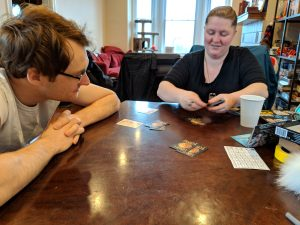 Photo of Emily's two friends, one of whom is Sidequest contributor E. Forney, playing Skull King on her dining room table. The background contains a bookshelf full of board games, a red couch, and a cat tower by the window.
