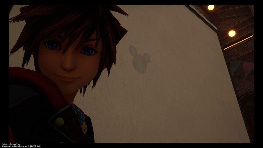 Sora takes a selfie in front of a Lucky Emblem embedded into the cinema screen at Twilight Town. Kingdom Hearts III, Square Enix, 2019.