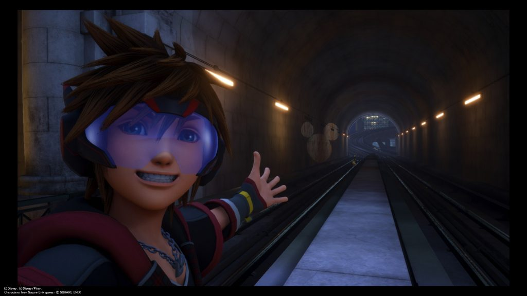 Sora takes a selfie in front of a Lucky Emblem projected at the end of a tunnel in San Fransokyo. Kingdom Hearts III, Square Enix, 2019.