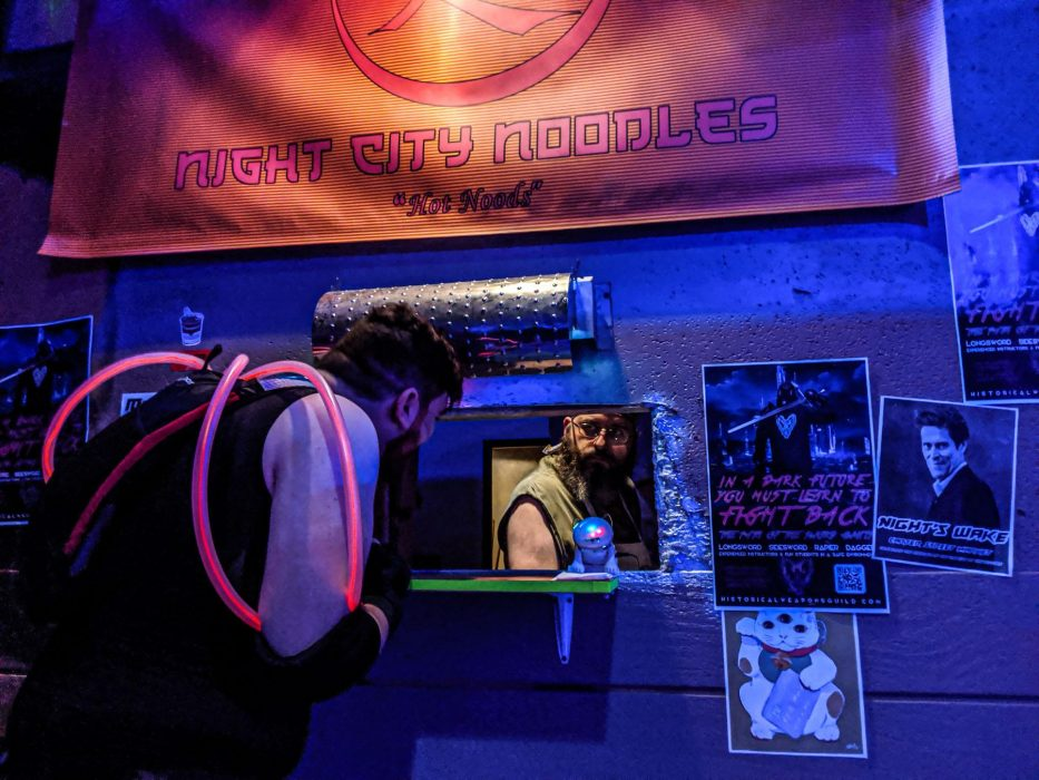 "A player crouches down to talk to the noodle vendor through the window of the noodle stand, which has a sign that reads ""Night City Noodles: Hot Noodz."""
