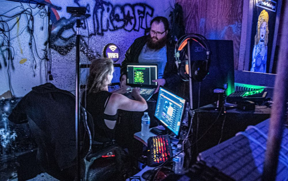 A hacker, surrounded by piles of computer equipment, takes a look at a puzzle on another player's the laptop screen. The room is dimly lit, with graffiti all over the walls and computer parts littered everywhere.