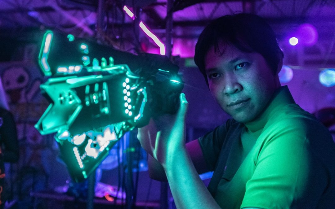 A player poses with an elaborate cyberpunk handgun, which glows with teal LEDs