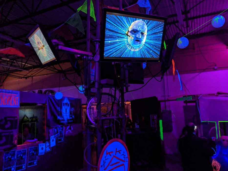 The blue face of AI Omicron is seen on the TV screens above Night City's blacklit main square in the airsoft arena.