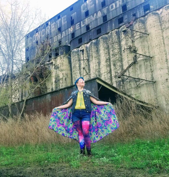 Jameson shows off their costume for Cyberpunk: Night City in front of a grain elevator. The costume includes a cape with a psychedelic lining, galaxy tights under jean shorts, a yellow top, and a jean vest. Jameson is white, with short blue hair and glasses.