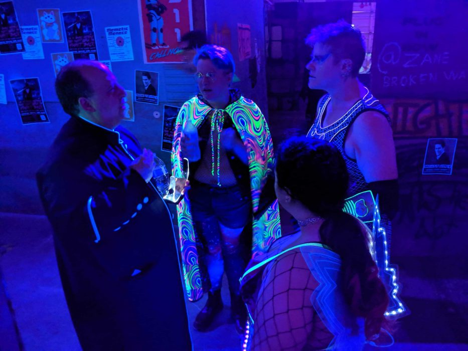Four members of the Children of Whisper gather in a small circle in the blacklit streets of Night City, talking with concern. Jameson's cape glows in the blacklight.