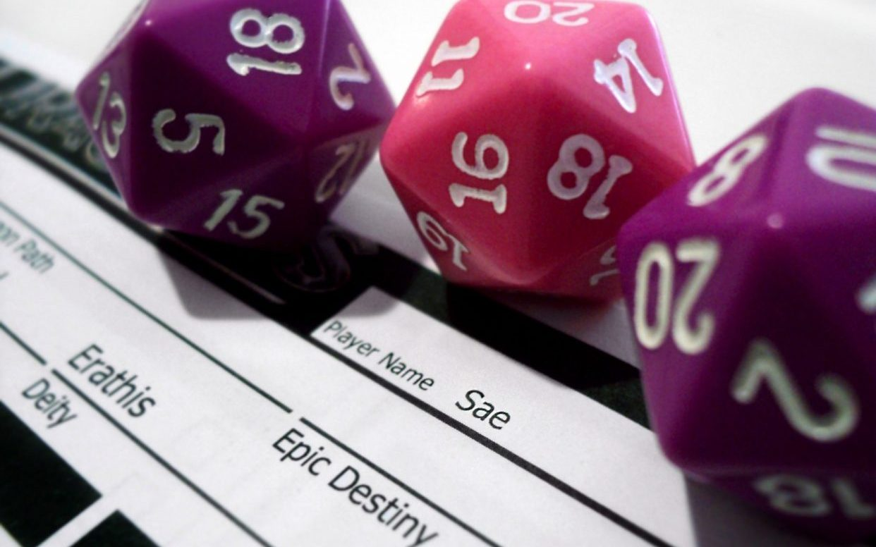 Two purple dice and one pink die on top of a Dungeons and Dragons character sheet.