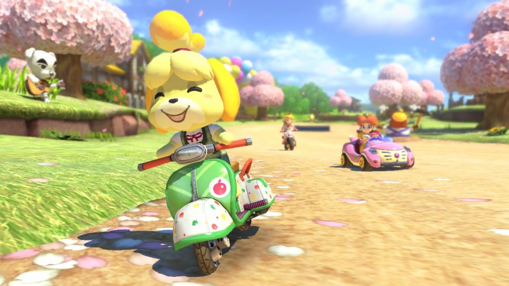 Isabelle (Animal Crossing), Princess Daisy, and Princess Peach (Mario series) race on the Animal Crossing course in Mario Kart 8 while K.K. Slider, an Animal Crossing villager, watches from the sidelines.