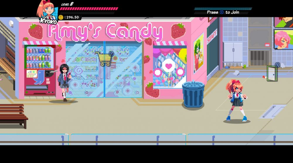 A screenshot of River City Girls. A girl sporting a red high ponytail in a ribbon stands in a fighting stance on the right side of the screen. Behind her stands a large trash can and a bright pink candy shop. Another girl, wearing a jacket over a school uniform, leans against the wall looking at her cell phone.