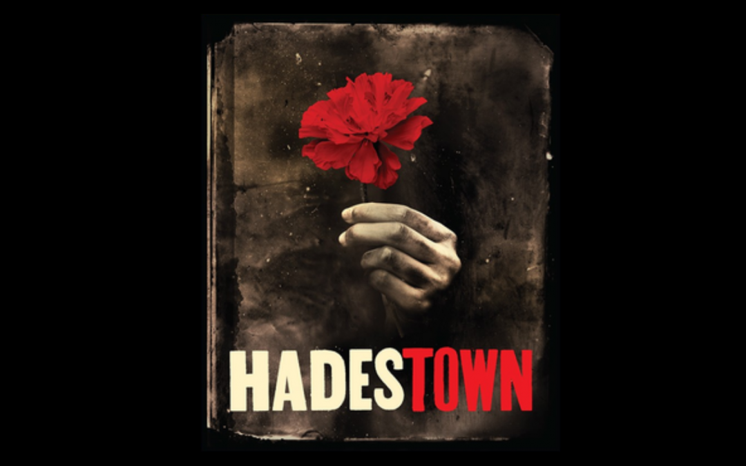 """The Hadestown poster, depicting a hand holding a red flower above the word """"Hadestown."""""""