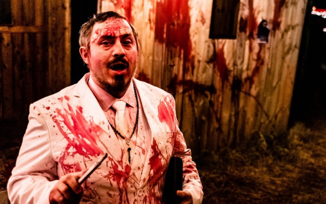 A photo of a person in a white tuxedo splattered with blood.