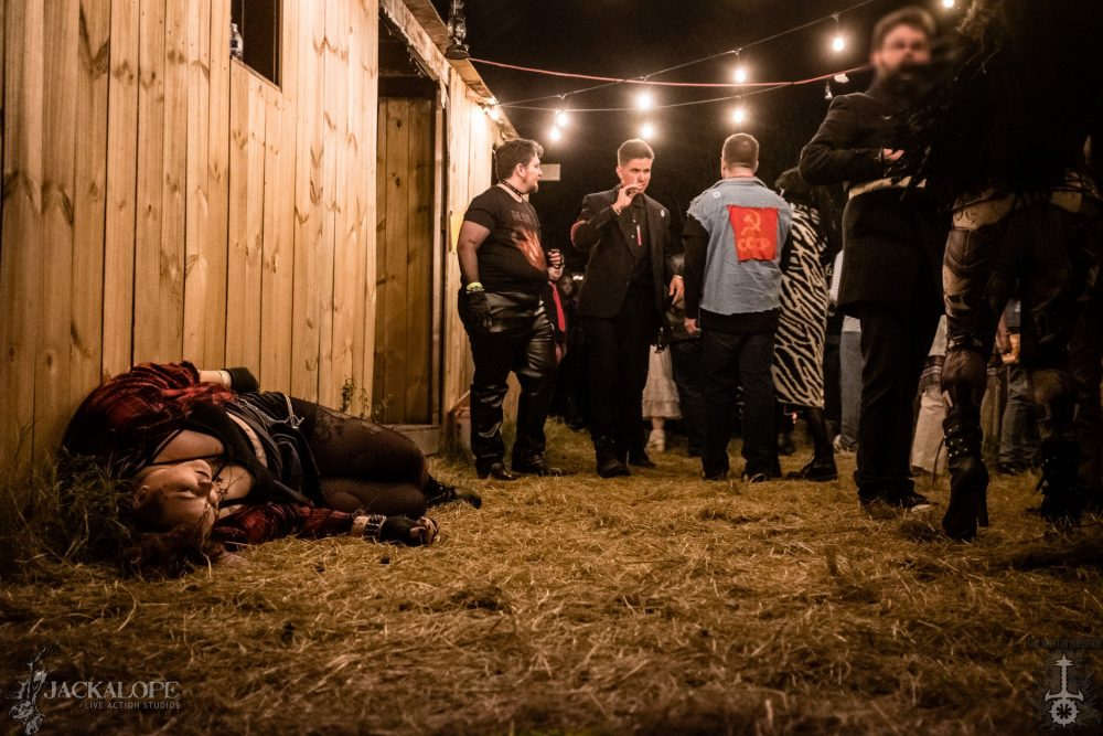 In the background, a group of LARPers dressed as vampires confer under a string of lights. In the foreground, a victim lies motionlessly in the straw.