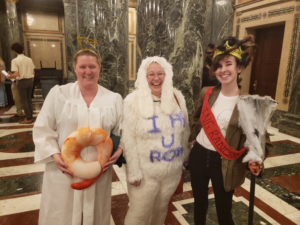 "A photo of E. Forney in a ""Shrimp Heaven Now"" costume, Emily Durham in an ""i h8 u ron"" costume, and a wonderful stranger who is dressed as King Rancho."