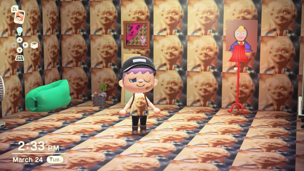 A screenshot from Nola's ACNH house, which is wallpapered entirely with tiled pictures of The Boy, a horrible image of a doll that looks vaguely like a babyfaced old man who wants to murder you. Nola is also wearing the image on their shirt.