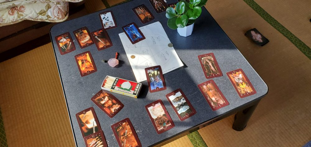 A photo of a small table with the pentagram, tarot cards, and other ritual items on top.