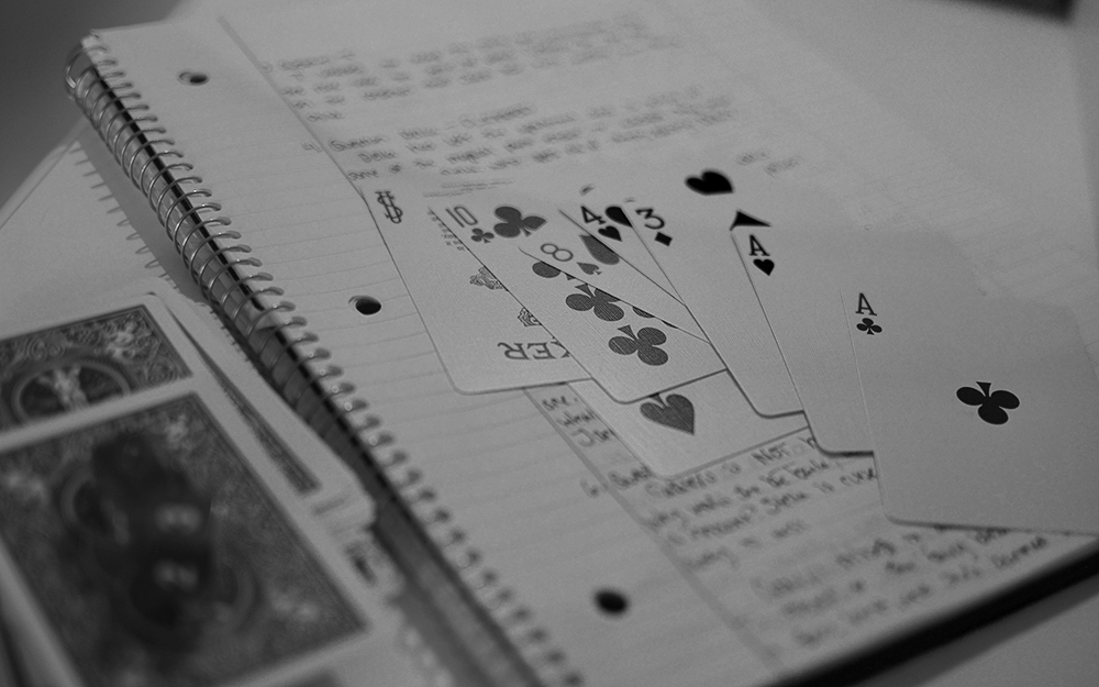 A photo of a hand of cards laid out against a notebook with indistinct writing. Photo by author.