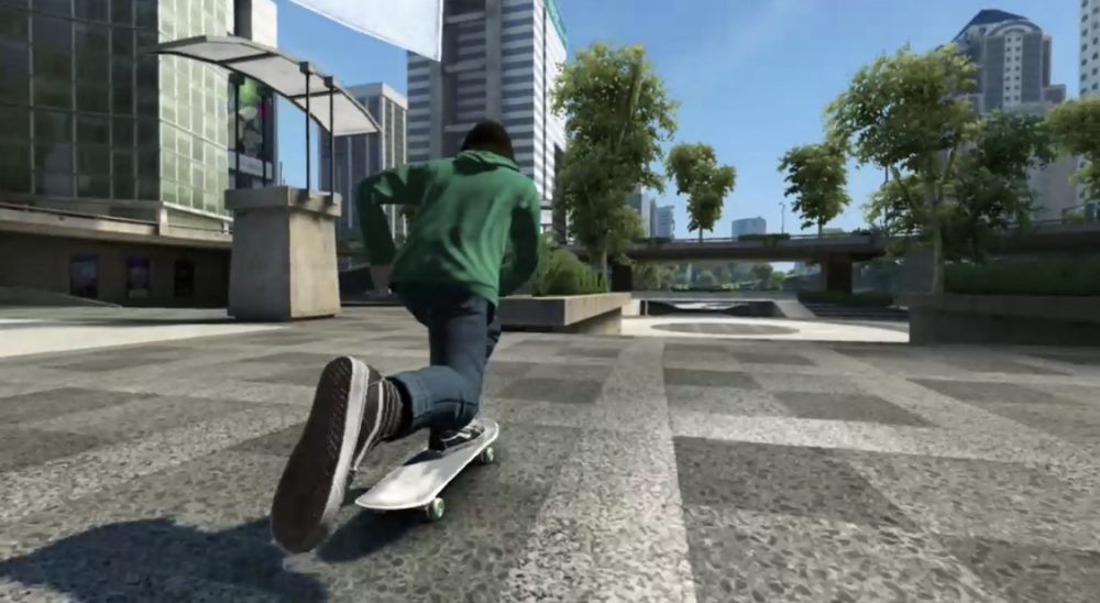 A screenshot from Skate 3. A skater in a green hoodie and jeans accelerates across concrete in a place with a lot of palm trees. The foreshortening is dramatic. Skate 3, EA Black Box, EA, 2010