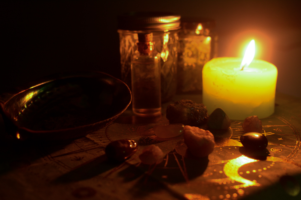 A photo of a candle burning next to jars of herbs, crystals, and an abalone shell.