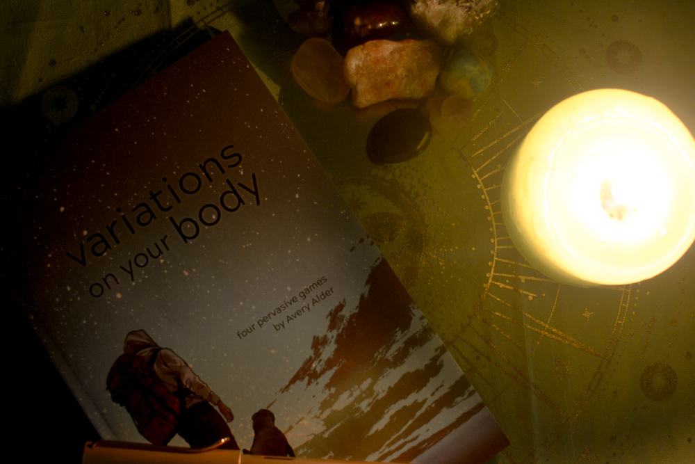 A photo of a candle burning next to some crystals, a journal, and a copy of Avery Alder's Variations on Your Body.