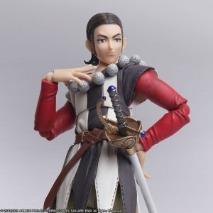 A doll of Sylvando from Dragon Quest XI, with a hand splayed against his collarbone, wearing a grey and white jester-like outfit with red sleeves. Dragon Quest XI: Echoes of an Elusive Age, Square Enix, 2017.